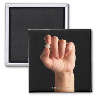 Las personas dan sostener una píldora blanca entre imán cuadrado