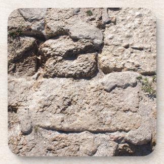 Las piedras de la piedra caliza en la playa posavasos