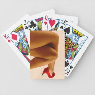 Las piernas desnudas cruzadas de la mujer con los  cartas de juego