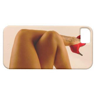 Las piernas desnudas cruzadas de la mujer con los  iPhone 5 cobertura