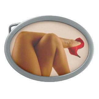 Las piernas desnudas cruzadas de la mujer con los  hebilla de cinturon oval