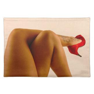 Las piernas desnudas cruzadas de la mujer con los  mantel individual