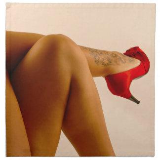 Las piernas desnudas cruzadas de la mujer con los  servilletas