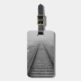 las pistas de ferrocarril se descoloran en la nieb etiquetas maleta