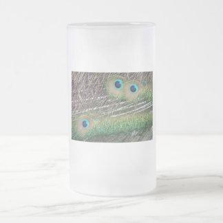 Las plumas del pavo real se cierran encima de jarra de cerveza esmerilada