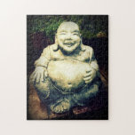 """Laughing Buddha Jigsaw Puzzle<br><div class=""""desc"""">This is a concrete figure of a happy and joyful,  round bellied Buddha in a garden setting with greenery bedding and bonsai plants in the background.</div>"""