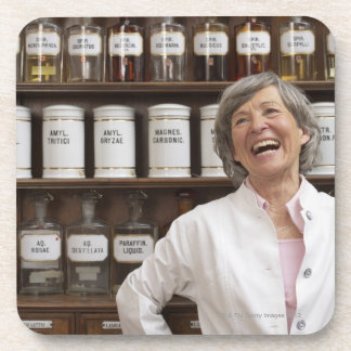 Laughing pharmacist standing in front of a shelf beverage coasters