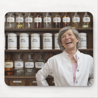 Laughing pharmacist standing in front of a shelf mouse pad