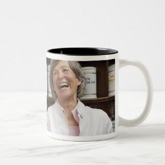 Laughing pharmacist standing in front of a shelf coffee mug
