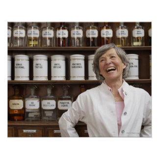 Laughing pharmacist standing in front of a shelf poster