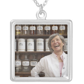Laughing pharmacist standing in front of a shelf silver plated necklace