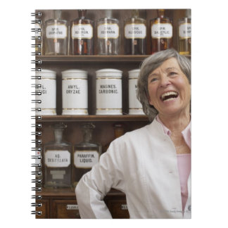 Laughing pharmacist standing in front of a shelf spiral notebook