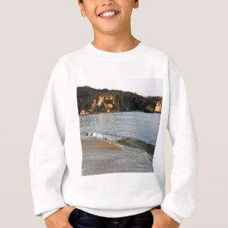 Lavado del mar de la playa encima sudadera