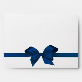 Lazo de satén azul elegante en el sobre blanco