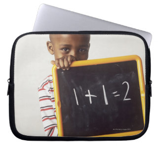 Learning arithmetic. 4-year-old boy holding a computer sleeve