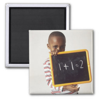 Learning arithmetic. 4-year-old boy holding a magnet