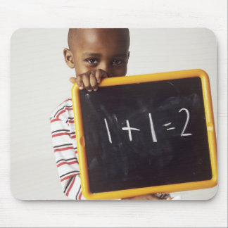 Learning arithmetic. 4-year-old boy holding a mouse pad