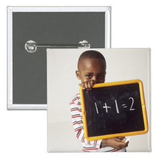 Learning arithmetic. 4-year-old boy holding a pinback button