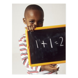 Learning arithmetic. 4-year-old boy holding a postcard