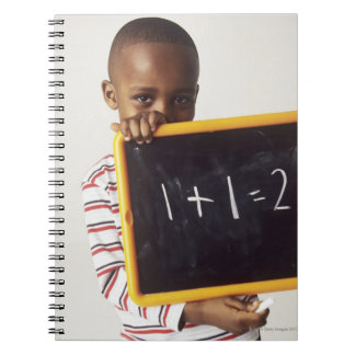 Learning arithmetic. 4-year-old boy holding a spiral notebook