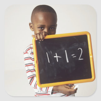 Learning arithmetic. 4-year-old boy holding a square sticker