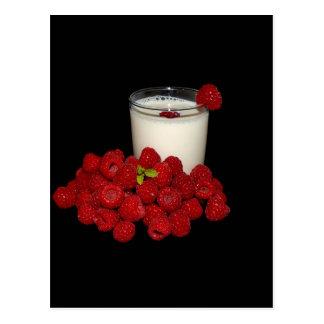 leche blanca con las frambuesas rojas en un negro postal