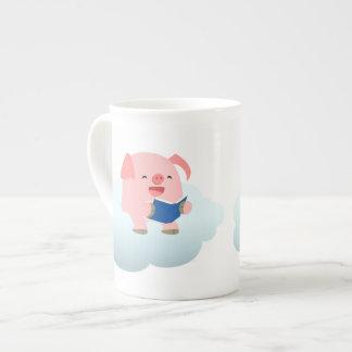 Lector lindo del cerdo del dibujo animado en la taza de porcelana
