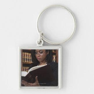 Lectura de la mujer en biblioteca jurídica llavero cuadrado plateado