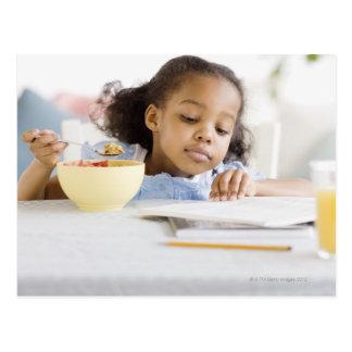 Lectura del chica de la raza mixta y desayuno de postales