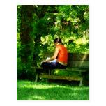 Lectura del chica en parque postal