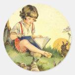 Lectura del muchacho debajo del árbol con los etiquetas redondas