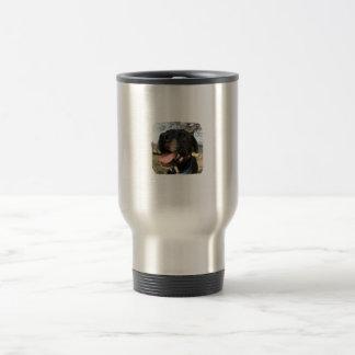Lengua del rosa del perro negro que sonríe en cáma tazas de café