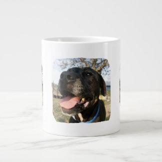 Lengua del rosa del perro negro que sonríe en cáma tazas extra grande