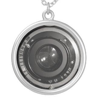 Lente de cámara del vintage en el collar plateado