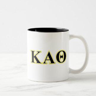 Letras amarillas y negras de la theta alfa de taza de café de dos colores