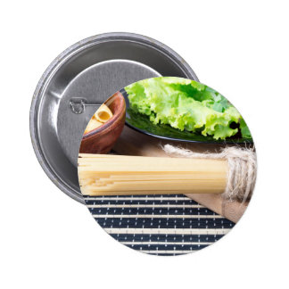 Lettuce in a black plate, pasta in a wooden bowl pinback button