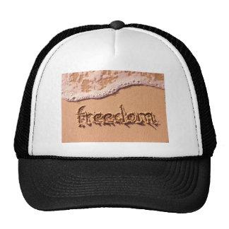 Libertad escrita dentro de la arena entre las onda gorras