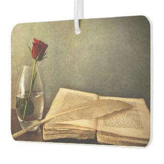 Libro antiguo y ambientador de aire color de rosa