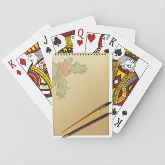 Libro de la mano con la pluma y el lápiz cartas de póquer