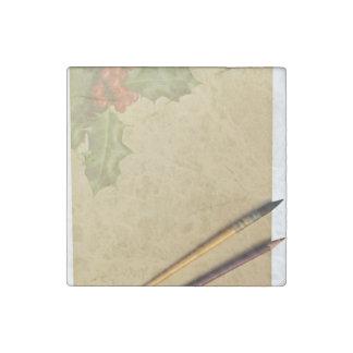 Libro de la mano con la pluma y el lápiz imán de piedra