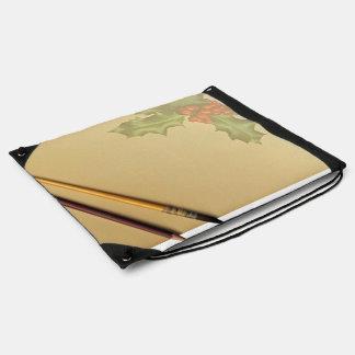 Libro de la mano con la pluma y el lápiz mochilas