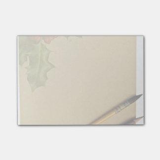 Libro de la mano con la pluma y el lápiz post-it® nota