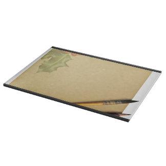 Libro de la mano con la pluma y el lápiz tabla para cortar