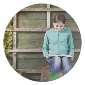 Libro de la sentada y de lectura del chica cerca platos