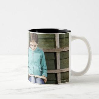 Libro de la sentada y de lectura del chica cerca taza de café de dos colores