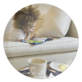 Libro de lectura del muchacho de la raza mixta en plato para fiesta