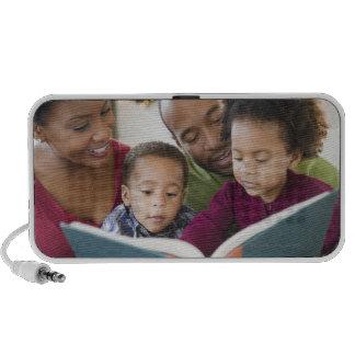 Libro de lectura negro de la familia junto laptop altavoces