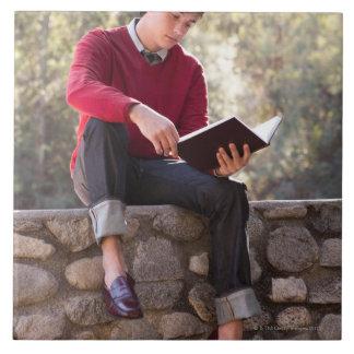 Libro y sentada de lectura del estudiante en la pa azulejo cuadrado grande