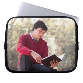 Libro y sentada de lectura del estudiante en la pa fundas computadoras