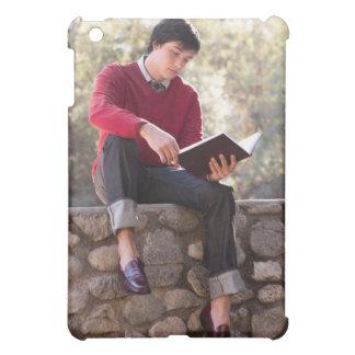 Libro y sentada de lectura del estudiante en la pa